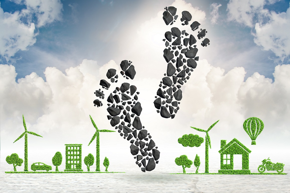 an illustration of a carbon footprint with buildings, trees, vehicles and wind turbines formed out of leaves
