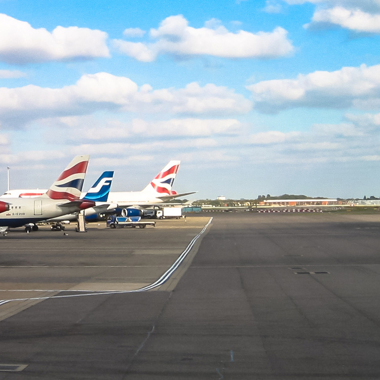 plane tails on runway at Heathrow with blue sky and clouds