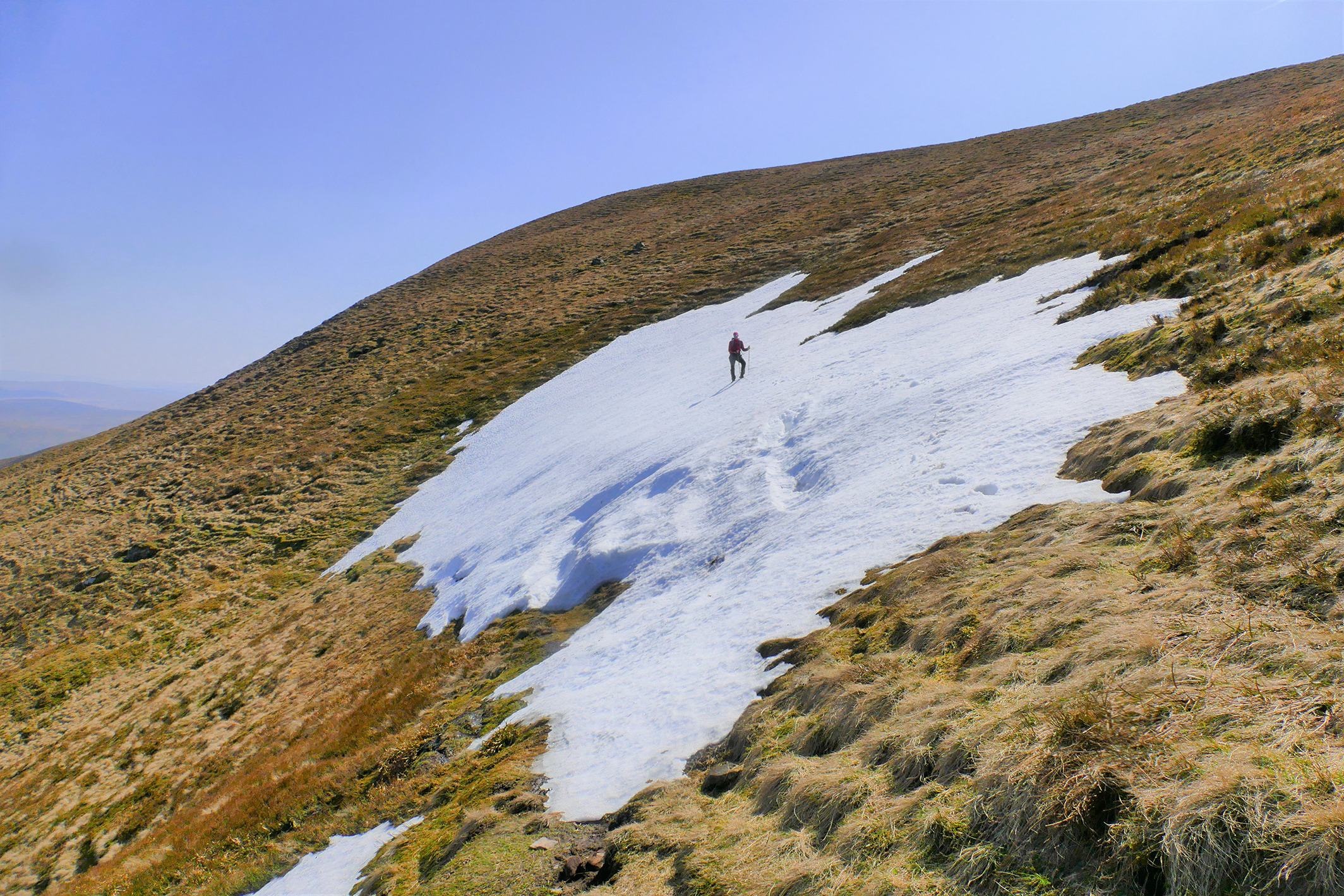 Author Iain Cameron stands on the last patch of snow south of the Central Belt, at Cramalt Craig on 22 April 2019. On this date, it was 50m long. (© Iain Cameron.)