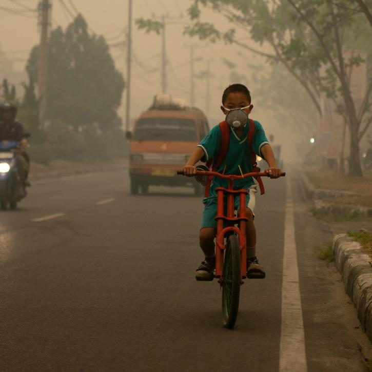 Boy cycling through smoke with a mask